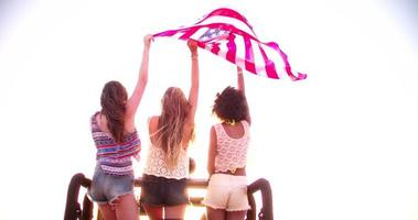 multi etnico gruppo di ragazze felicemente battenti una bandiera americana video