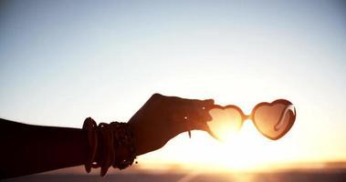 Mano sujetando gafas de sol en forma de corazón en una playa al atardecer