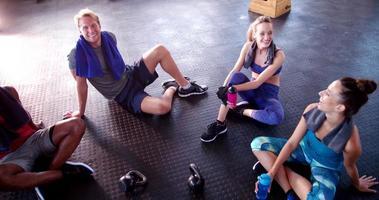 Gruppe multiethnischer Freunde, die sich im Fitnessstudio erholen und Feuchtigkeit spenden