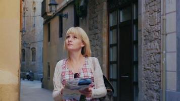 turista femminile con una mappa è nel centro storico. ammirando i palazzi, cercando la strada. il quartiere gotico di barcellona