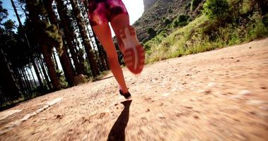 Athlete running on a mountain dirt road in early light video