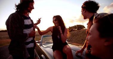 amici boho adolescenti che abbracciano e ridono al tramonto