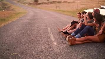 amigos estilo boho descansando encostados em um conversível vintage na estrada video