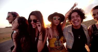 amici boho adolescenti seduti su una capote al tramonto