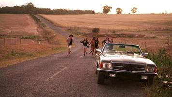 amici adolescenti che corrono fuori al tramonto verso la loro auto