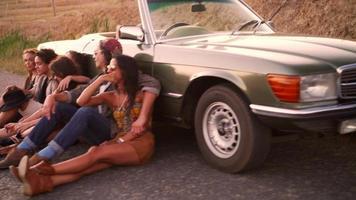 amigos estilo boho relaxando em uma estrada rural ao pôr do sol video