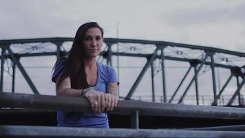 una hermosa niña de pie cerca de un río con un puente detrás de ella