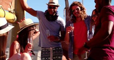 uomo dai capelli lunghi in occhiali da sole festeggiare con gli amici su uno yacht