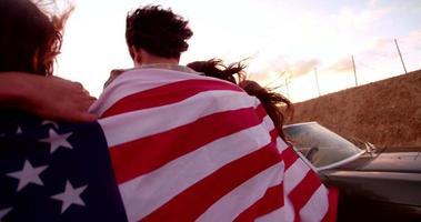 Amigos hipster caminando por la carretera con una bandera americana