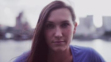 close-up de uma linda garota na frente de uma paisagem urbana, câmera lenta video