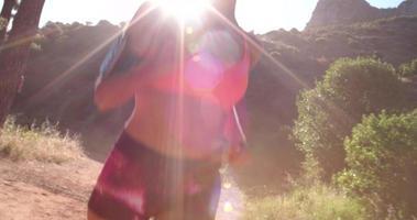 Emparejador escuchando auriculares en un sendero de montaña por la mañana video