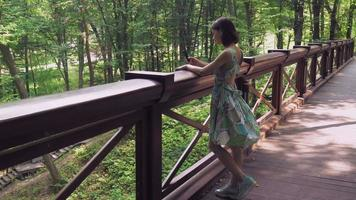 Une fille se tient à la rampe sur la passerelle dans le parc et écrit du courrier