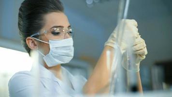 Young female scientist holding tube à essai avec échantillon liquide faisant de la recherche en laboratoire clinique