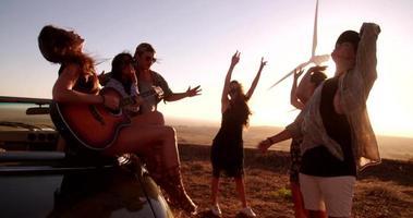 Amigos hipster disfrutando de un viaje por carretera con una guitarra durante la puesta de sol