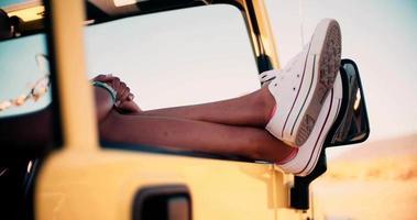 Beine und Füße ragen auf der Straße aus dem Autofenster