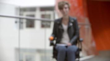 Female university student in a wheelchair moving into focus