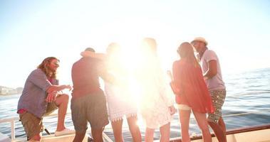 multietnico gruppo di amici guardando l'orizzonte da uno yacht