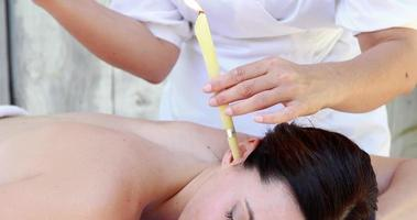 Relaxed brunette getting an ear candling treatment video