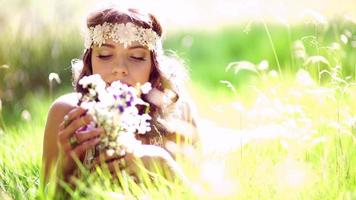 Smiling hippie girl lying in grass holding wild flowers video