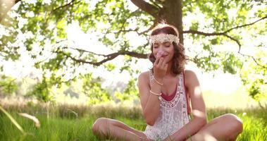 garota hippie cheirando uma flor em um parque de verão