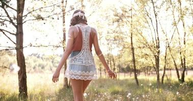 Boho Mädchen, das durch Sommerpark geht, der sich frei fühlt