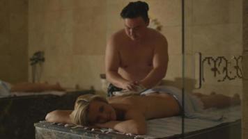 giovane bella femmina è rilassante durante un massaggio con sapone turco in un centro benessere termale.