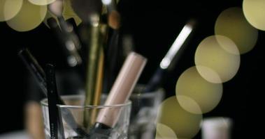 make-up objecten en hand pen terug in een glas. video