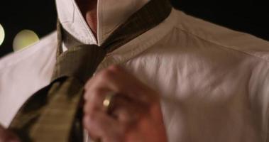 hombre atándose la corbata por sí mismo. de cerca y en cámara lenta. video