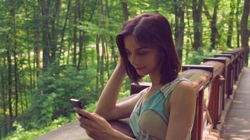 Brünette Frau ruht auf einem Holzgeländer an den Ellbogen und eine Nachricht auf der Zelle