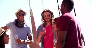 Freunde lachen, trinken und genießen eine Sommerparty im Freien