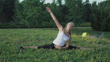 Jeune blonde élancée en chemise effectue un exercice d'inclinaison sur la colline avec de l'herbe verte dans le parc