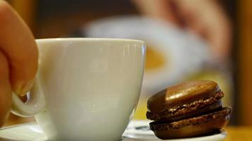 tazza di caffè con macaron marrone in una caffetteria al coperto video