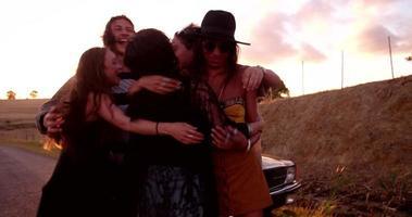 amici adolescenti che saltano e fanno festa fuori al tramonto