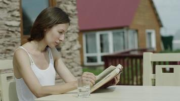 junge attraktive Frau, die Buch durch den Baum im Park liest, Dolly erschossen