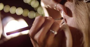 maquilladora aplica rímel en el ojo de la mujer en primer plano y cámara lenta. video