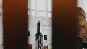duas jovens conversando à mesa com bebidas alcoólicas no terraço de uma casa de campo