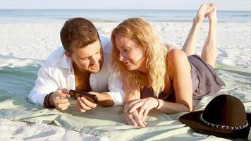 una coppia seduta sulla spiaggia usando i loro telefoni cellulari e parlando tra loro