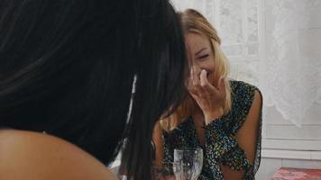meninas morenas e loiras conversando à mesa no terraço de uma casa de campo