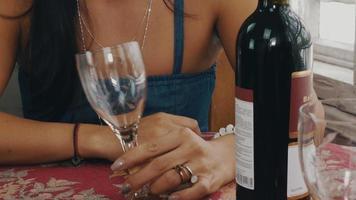 garota conversando à mesa com uma garrafa de vinho no terraço da casa de campo. copo vazio