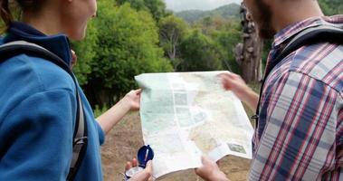 Vue arrière des randonneurs à la recherche d'une carte avec une boussole