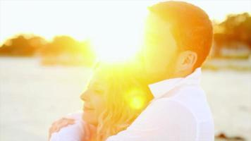 A couple embracing on the beach at sunset