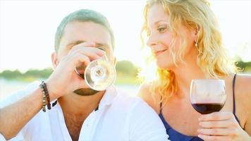 um casal bebendo vinho na praia ao pôr do sol