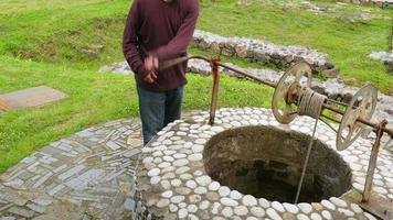 Hombre tomando agua del pozo histórico de la fuente, contenedor de barril de cuerda