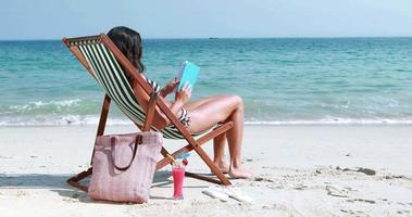 Jolie brune lisant un livre sur une chaise longue