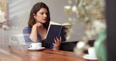Girl Drinking Coffee and Reading Book in Cafe video