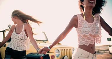 Afro-Mädchen, das Hände mit Freunden auf Strandstraße hält
