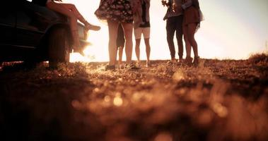 grupo de amigos adolescentes conversando ao pôr do sol durante a ponta da estrada