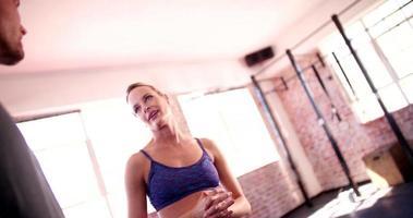 Freunde reden und scherzen während einer Pause im Fitnessstudio video