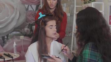 cabeleireira e artista visagista trabalhando na aparência de modelo. video