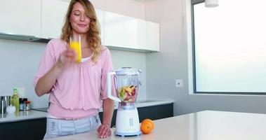 hübsche Frau in der Küche, die neben Entsafter Orangensaft trinkt